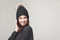 Friendly happy woman wearing a pompom hat pretty young knitted winter looking at the camera with lovely warm smile on grey with Royalty Free Stock Images