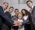 Friendly harmonious business team six people join hands and smiling focus is on hands but face expression is recognisable Stock Photo