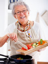 Friendly older woman happily cooking a meal Stock Images