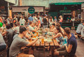 Friendly party with crowd of eating people at table during outdoor Street Food Festival Royalty Free Stock Photo