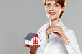 Friendly real estate agent presenting a model house and keys isolated on grey Stock Photos