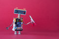 Friendly robotic handyman toy with red pliers. Pink background copy space Royalty Free Stock Photo