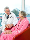 Friendly senior male doctor chatting to a patient an elderly women sitting in her pink dressing gown smiling as they discuss her Stock Images