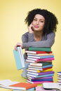 Friendly smiling girl along with colorful books. Royalty Free Stock Photo