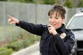Friendly smiling hispanic female officer as talks her radio as points Royalty Free Stock Images