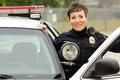 Friendly smiling hispanic female officer her patrol car Royalty Free Stock Images
