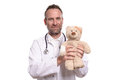 Friendly smiling paediatrician holding a teddy bear middle aged male with unshaven stubble with bandaged arm to reassure young Stock Images