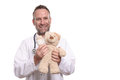 Friendly smiling paediatrician holding a teddy bear middle aged male with unshaven stubble with bandaged arm to reassure young Royalty Free Stock Photography