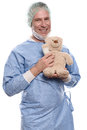 Friendly smiling paediatrician holding a teddy bear middle aged male wearing blue scrubs with bandaged arm to reassure young Stock Photo
