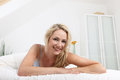 Friendly smiling woman on her bed Royalty Free Stock Image