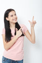 Friendly smiling woman pointing at copyspace isolated on white background Royalty Free Stock Photo