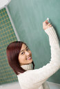 Friendly student or teacher writing on a board young blank green blackboard giving the camera beautiful smile Royalty Free Stock Photos