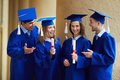 Friendly talk group of smart students in graduation gowns having chat Royalty Free Stock Image