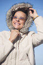 Friendly woman warm winter jacket portrait happy attractive mature wearing seasonal with hood and sunglasses joyful smiling with Royalty Free Stock Image
