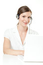 Friendly young woman with headset and laptop wearing a white blouse Royalty Free Stock Photo