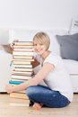 Friendly young woman with a stack of books tall hardcover sitting cross legged on the wooden floor in her living room Stock Image