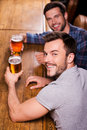 Friends in bar top view of two happy young men drinking beer at the counter and smiling Stock Photo