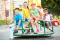 Friends on carousel image of little sitting and looking at camera Royalty Free Stock Photos