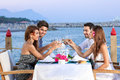 Friends celebrating at a seaside restaurant group of four seated table raising their wineglasses in toast with the ocean and Stock Image