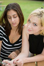 Friends on Cell Phone together (Beautiful Young Blonde and Brune Royalty Free Stock Image