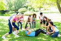 Friends cheering man doing sit ups group of men in the park Stock Photos