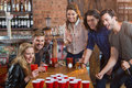 Friends cheering while woman playing beer pong in bar Royalty Free Stock Photo