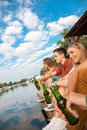 Friends chilling near lake group of cheerful Royalty Free Stock Images