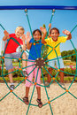Friends at a city playground cheerful climbing the net Royalty Free Stock Photos