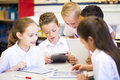 Friends in the classroom happy students using a digital tablet they are all wearing uniforms Stock Photo