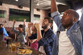 Friends At Counter In Sports Bar Watch Game And Celebrate
