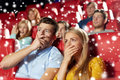 Friends or couple watching horror movie in theater Royalty Free Stock Photo