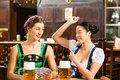 Friends drinking beer in bavarian pub playing cards tracht dirndl and lederhosen a fresh bavaria germany Royalty Free Stock Images