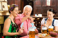 Friends drinking beer in bavarian pub playing cards tracht dirndl and lederhosen a fresh bavaria germany Stock Image