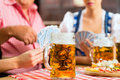 Friends drinking beer in bavarian pub playing cards tracht dirndl and lederhosen a fresh bavaria germany Royalty Free Stock Photography