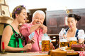 Friends drinking beer in bavarian pub playing cards tracht dirndl and lederhosen a fresh bavaria germany Stock Photo