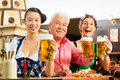 Friends drinking beer in bavarian pub tracht dirndl and lederhosen a fresh bavaria germany Royalty Free Stock Images