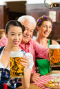 Friends drinking beer in bavarian pub tracht dirndl and lederhosen a fresh bavaria germany Royalty Free Stock Photo