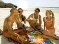Friends drinking beer on the beach at sandy Stock Photography