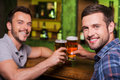 Friends drinking beer two cheerful young men toasting with and smiling while sitting together at the bar counter Stock Photography