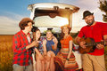 Friends drinking and playing guitar after car trip Royalty Free Stock Photo