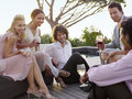 Friends drinking and socialising on porch group of multiethnic Stock Photos