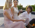 Friends drinking and socialising on porch three young Royalty Free Stock Photo