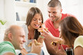 Friends eating pizza four enjoying to together at home party Stock Photo