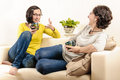 Friends enjoying coffee home chat laughing two women on sofa at person laugh good time relaxation vacation free Royalty Free Stock Images