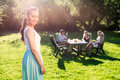 Friends enjoying garden party on a sunny afternoon young women standing in while her in background Royalty Free Stock Images