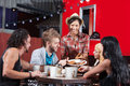 Friends enjoying pizza for late night snack Royalty Free Stock Images