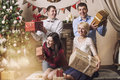 Friends of four men and women give gifts in the Christmas interi Royalty Free Stock Photo