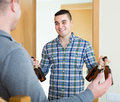 Friends gathering to drink beer at home two adult smiling male Stock Photo