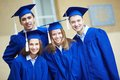 Friends in graduation gowns friendly students looking at camera Royalty Free Stock Images