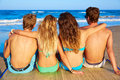 Friends group couples sitting in beach sand rear view back looking to the sea Stock Photo